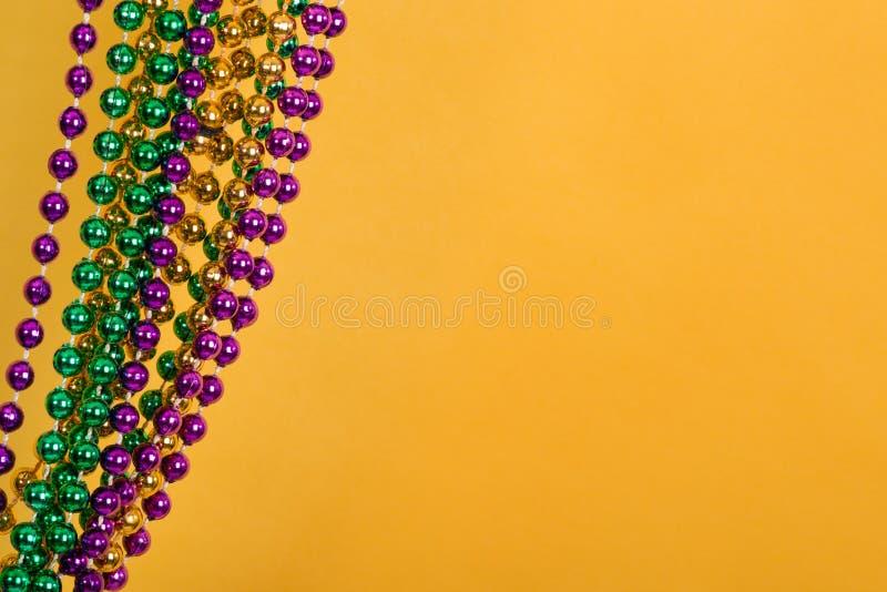 Grânulos de Mardi Gras contra o fundo amarelo dourado imagens de stock royalty free