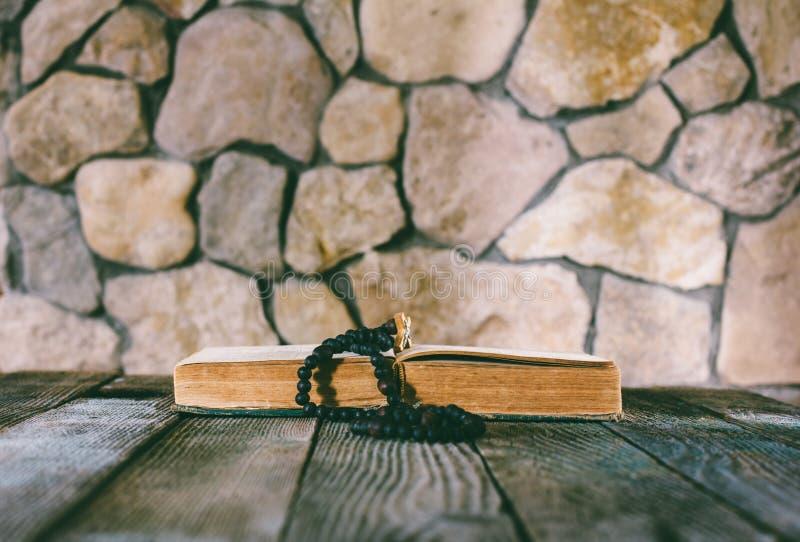 Grânulos de oração com uma cruz em um livro velho aberto na tabela de madeira velha em um fundo das paredes de pedra imagem de stock royalty free