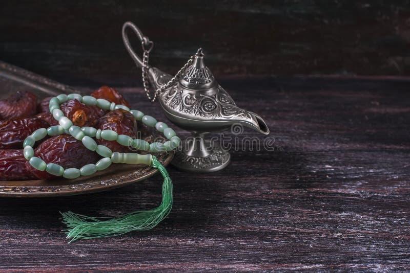 Grânulos de oração islâmicos verdes, datas e lâmpada de prata do ` s do aladdin em um fundo de madeira escuro Conceito da ramadã fotografia de stock royalty free