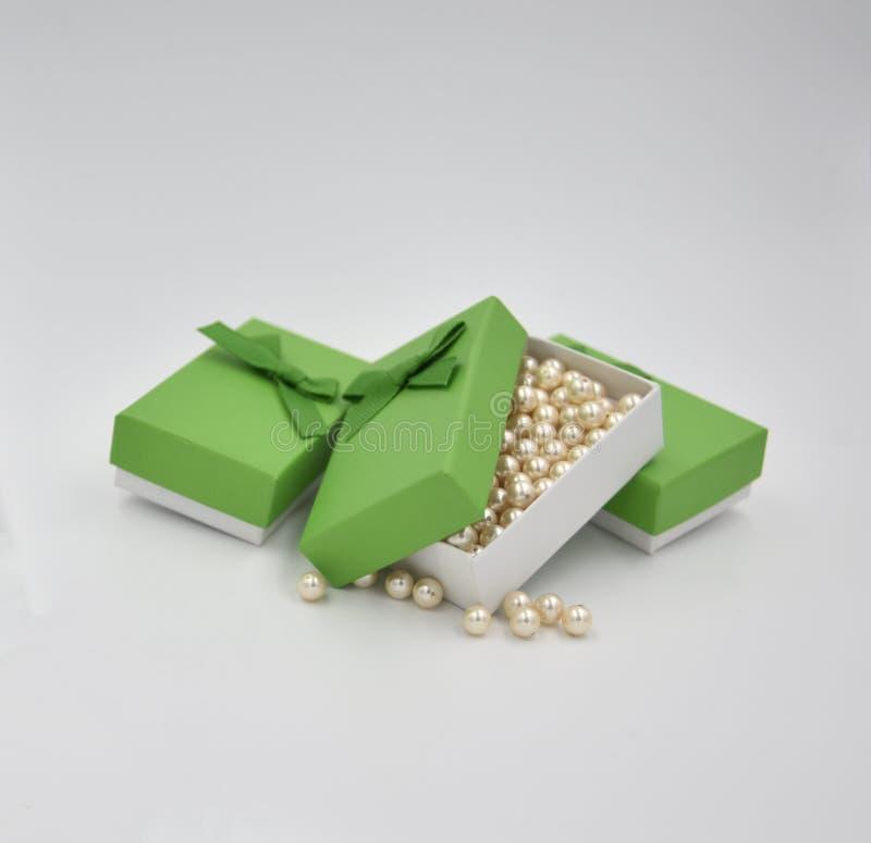 Grânulos dourados amarelos da bola do marfim na caixa de presente verde com outras duas caixas de presente verdes com curva fotos de stock