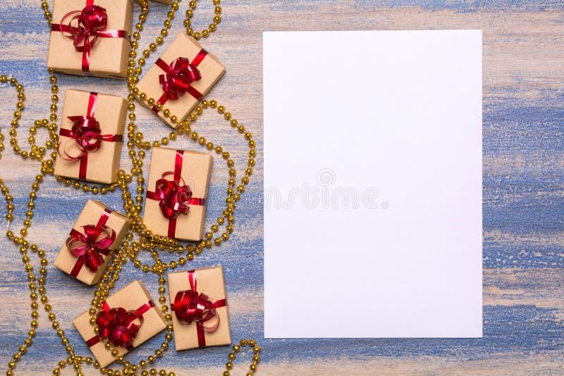 Grânulos dourados, presentes envolvidos no papel de embalagem com uma curva vermelha e papel vazio fotografia de stock