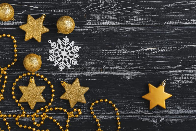 Grânulos, estrelas e flocos de neve do Natal em um fundo rústico de madeira preto Vista superior, configuração lisa foto de stock