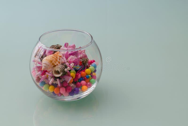 Grânulos, joia e acessórios em um vaso de vidro em um fundo de turquesa Bordado com crianças imagem de stock