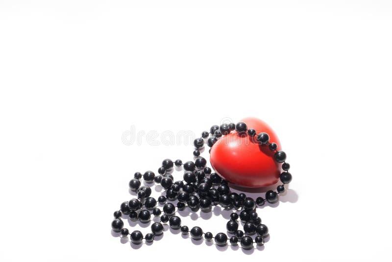 Grânulos pretos e um coração vermelho no fundo branco fotografia de stock