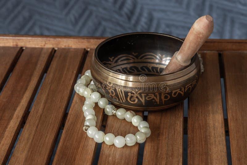 Grânulos tibetanos da bacia e do jade do canto em um suporte de madeira foto de stock