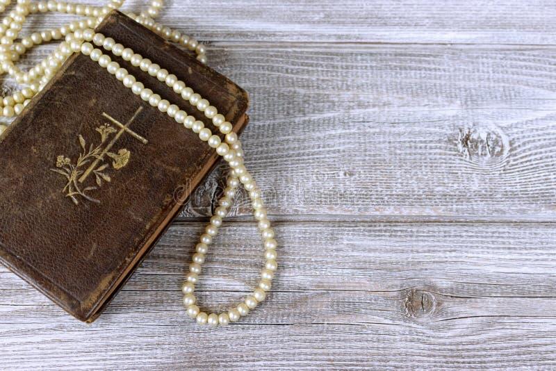 Grânulos velhos da Bíblia Sagrada e do rosário na tabela de madeira rústica imagem de stock royalty free