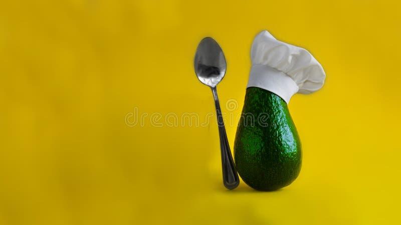 Grüne frische Avocado im Hut des sauberen weißen Chefs mit Metallteelöffel auf gelbem leerem Hintergrund Horizontale Fahne mit Ko stockbilder