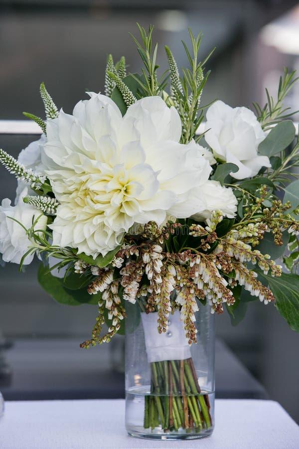 Grüner und weißer Heiratsblumenstrauß in einem Glas wasser- Heiratsblumen-Reihe stockfoto