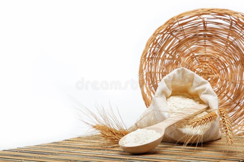Grão da farinha e do trigo com colher de madeira. fotos de stock royalty free