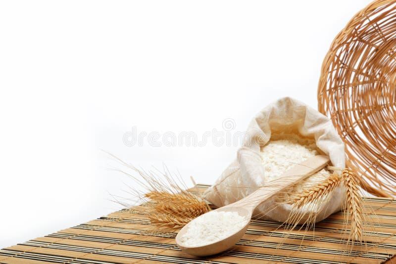 Grão da farinha e do trigo com colher de madeira. imagens de stock royalty free