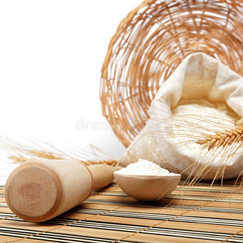 Grão da farinha e do trigo com colher de madeira imagens de stock royalty free