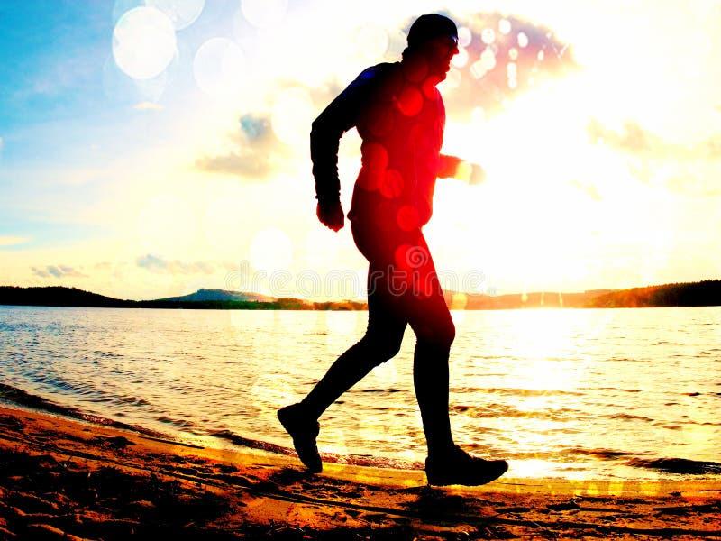 Grão do filme O homem alto com sunglass e o tampão escuro está correndo na praia no por do sol foto de stock royalty free
