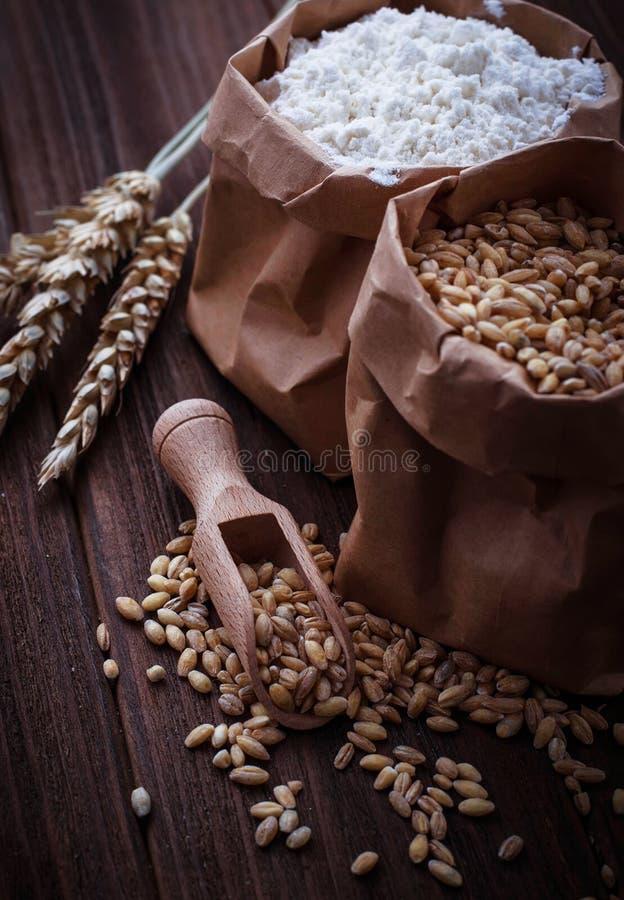 Grão e farinha do trigo em uns sacos de papel fotografia de stock