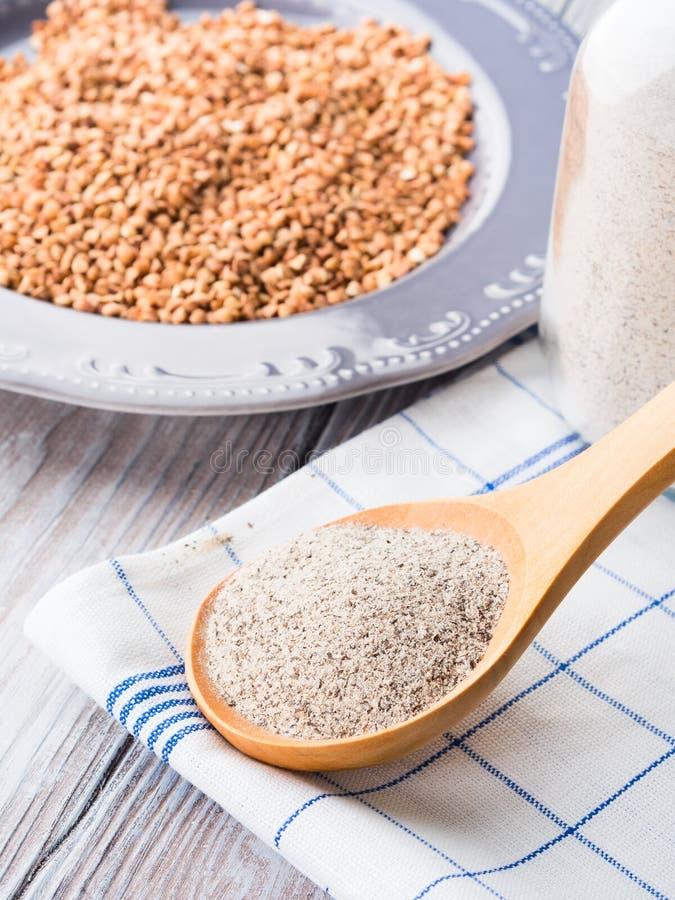 Grão e farinha do trigo mourisco na tabela de madeira imagens de stock royalty free