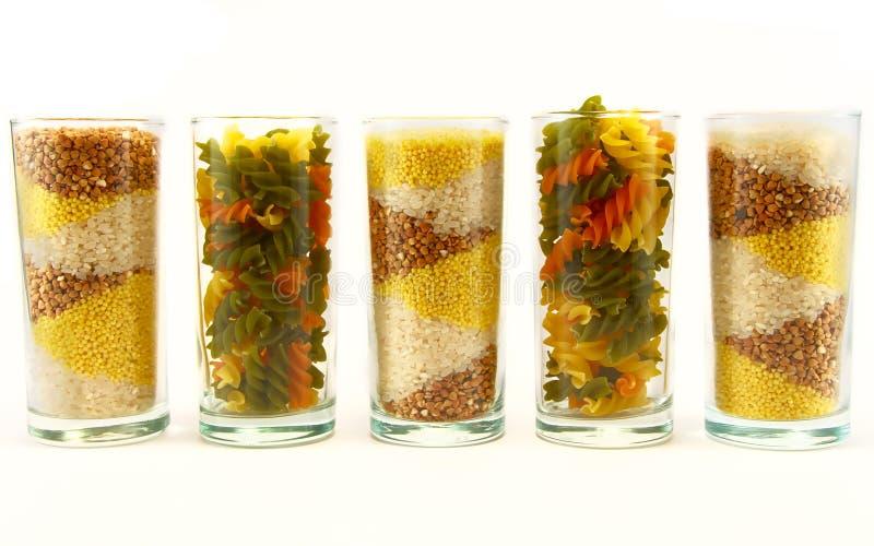 Grão e massa em uns copos em um fundo branco imagens de stock