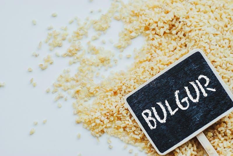 Grão e quadro crus do trigo do bulgur orgânico com bulgur da palavra fotos de stock