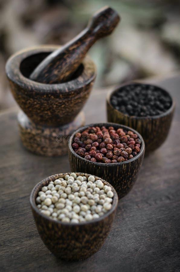 Grãos brancos orgânicos da pimenta vermelha e preta na exposição de madeira imagens de stock