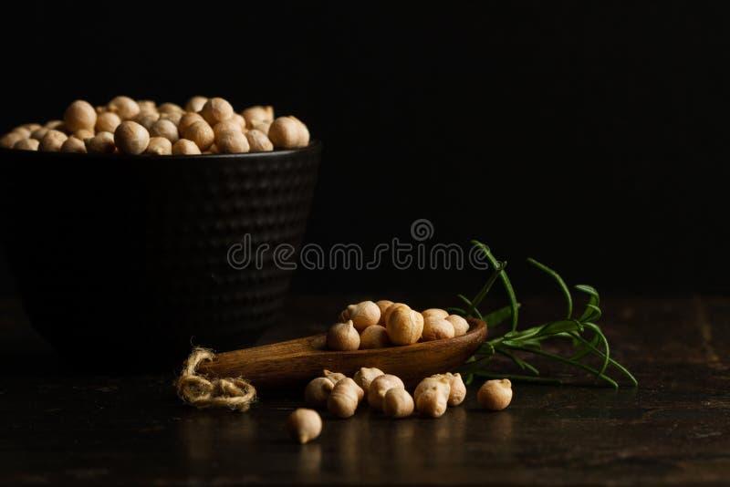 Grãos-de-bico em um bowland cerâmico preto em uma colher de madeira fotografia de stock royalty free