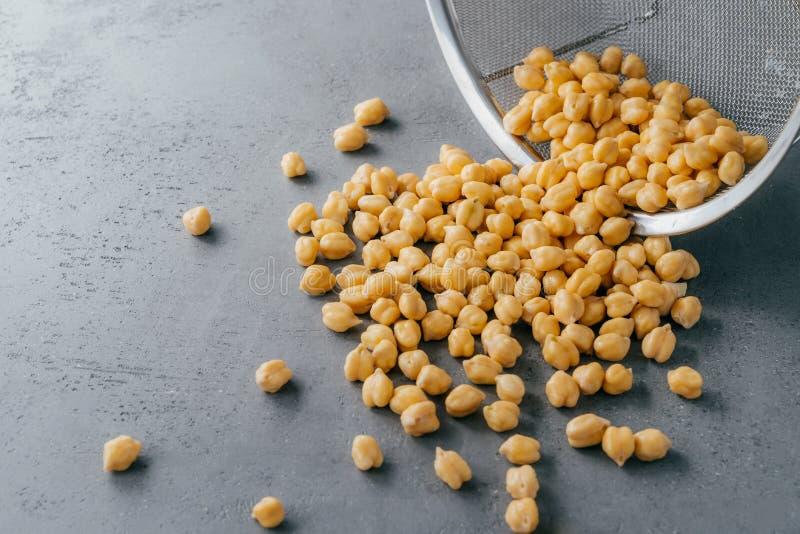 Grãos-de-bico limpos secos derramados no fundo cinzento da peneira Ingredientes de alimento para vegetarianos Sementes úteis Prod imagens de stock