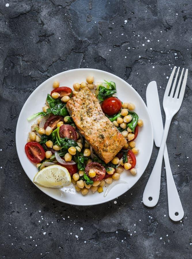 Grãos-de-bico mornos, tomates de cereja, salada dos espinafres e salmões cozidos - almoço saudável em um fundo escuro, vista supe fotografia de stock royalty free