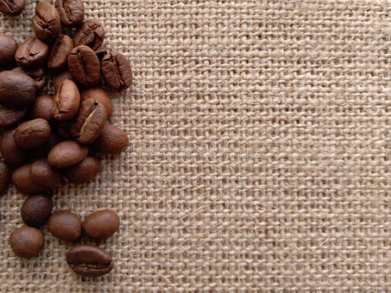 Grãos de café no byurlap Superfície disponível fotografia de stock