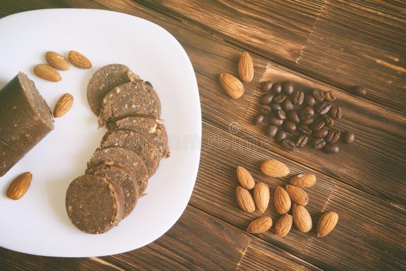 Grãos de café, porcas da amêndoa e salsicha da pastelaria do chocolate em uma superfície de madeira Ainda vida rústica fotografia de stock royalty free