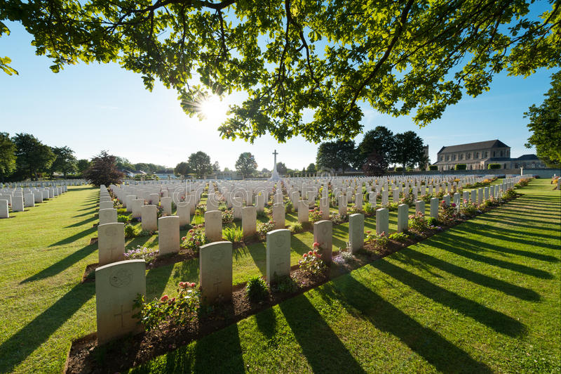 Gräber und Baum in der Hintergrundbeleuchtung, in einem englischen Militärfriedhof in Normandie, bei Ranville lizenzfreie stockfotos