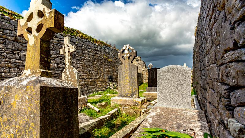 Gräber zwischen ruinierten Wänden im Friedhof der mittelalterlichen Kirche von Killilagh im Dorf von Doolin lizenzfreies stockbild