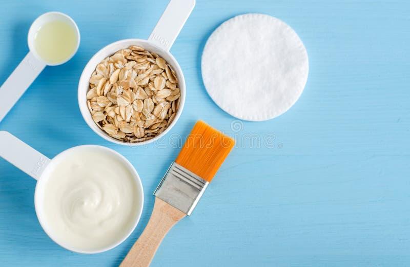 Gräddfil- eller grekyoghurt, rullande havre och olivolja i små skopor för en plast- - ingredienser för att förbereda diy maskerin arkivfoton