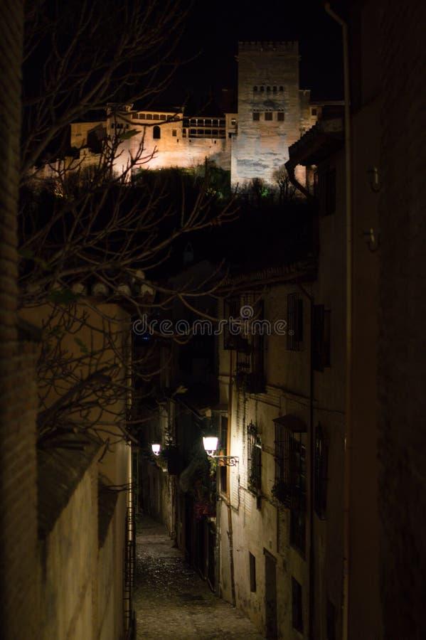 Gränd i den gamla moriska fjärdedelen AlbaicÃn i Granada, Spanien på natten med sikt på Alhambra royaltyfria bilder