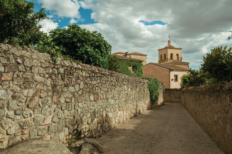 Gränd i en molnig dag med stenväggar som går in mot Santa Maria la Mayor Church och kyrktorn på Trujillo royaltyfria bilder