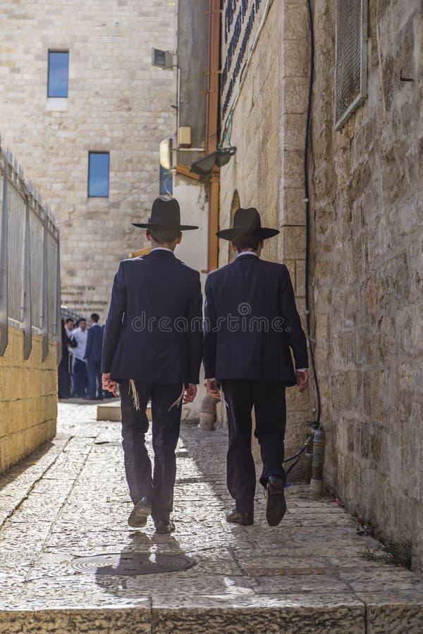 Gränd i Jerusalem den gamla staden med två ortodoxa pojkar som bort går royaltyfria foton