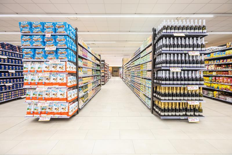 Gränder av hyllor med gången av godsprodukter inom en supermarket arkivfoton