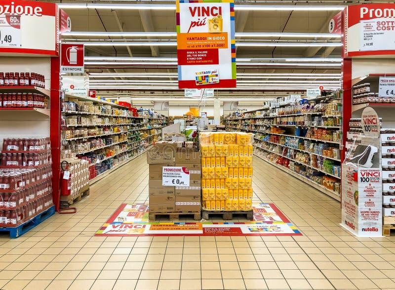 Gränder av hyllor med godsprodukter inom av IPEREN av den Varese stormarknaden Frukostavdelning med bröd- och mjölräknare I arkivbild