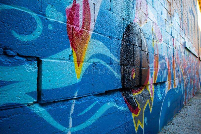 Grändväg med grafitti på en tegelstenvägg arkivfoton