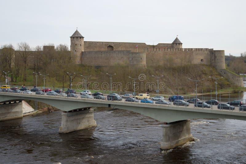 Gränsövergång bro mellan Ryssland och Estland till och med den Narva floden på bakgrunden av den Ivangorod fästningen, molnig dag fotografering för bildbyråer