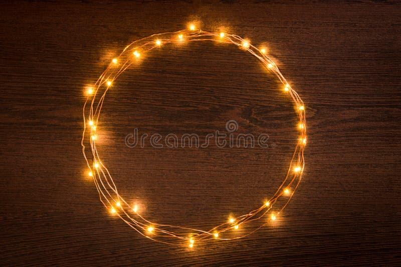 Gräns för girland för julljus rund över mörk träbakgrund Lekmanna- lägenhet, kopieringsutrymme arkivfoton