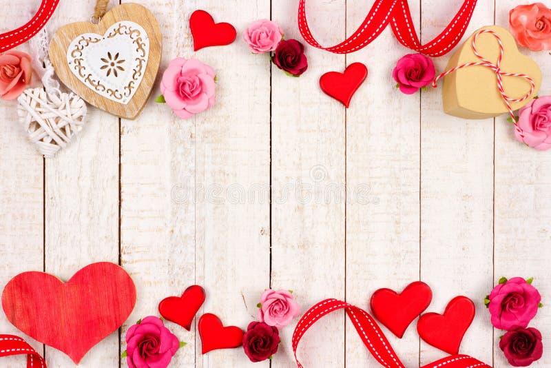 Gräns för valentindagdubblett av hjärtor, blommor, gåvor och dekoren på vitt trä fotografering för bildbyråer