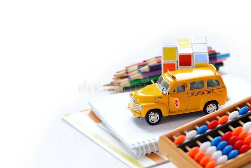 Gränsar den övre sikten för slutet av färgrik baksida för den gula bussen till skolatillförsel över den vita tabellen Utrymme för arkivfoton