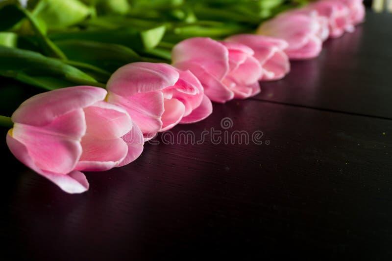 Gränsen från ljusa rosa tulpan blommar på svart träbakgrund arkivfoton