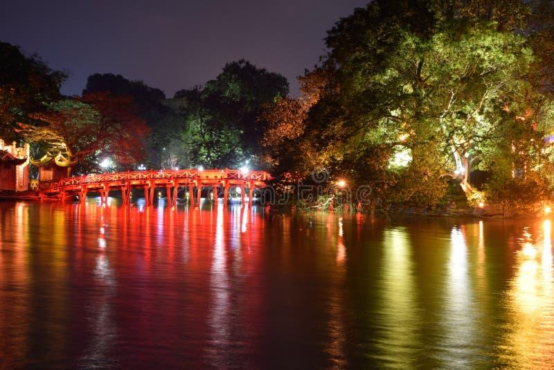 Gränsmärke av Hanoi - den Huc bro- och Hoan Kiem sjön i natten på Hanoi, Vietnam arkivbilder