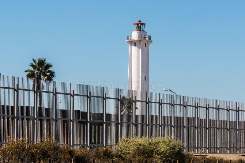 Gränsstaket Separating San Diego och Tijuana med fyren royaltyfri foto