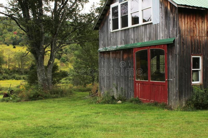 Gräs- fält med den lilla konverterade ladugården med röda dörrar och fönster royaltyfri bild