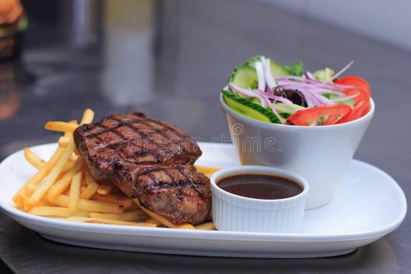 Gräs Fed Rump Steak med chiper sallad och pepparsås royaltyfri fotografi