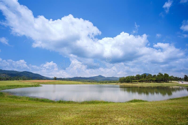 Gräsfältet och den lilla sjön med molnig och blå himmel över på Singha parkerar fotografering för bildbyråer