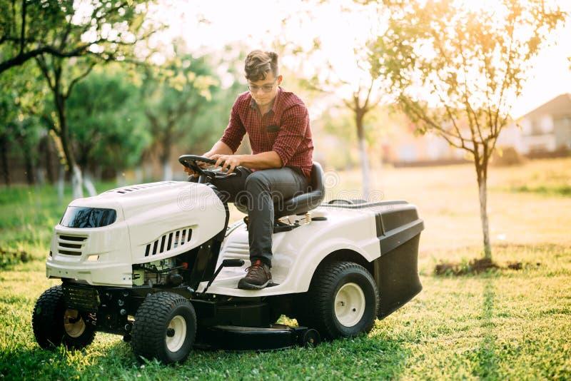 gräsklipparetraktoren med arbetaren som gör att landskap, fungerar på helgsolnedgången royaltyfri fotografi