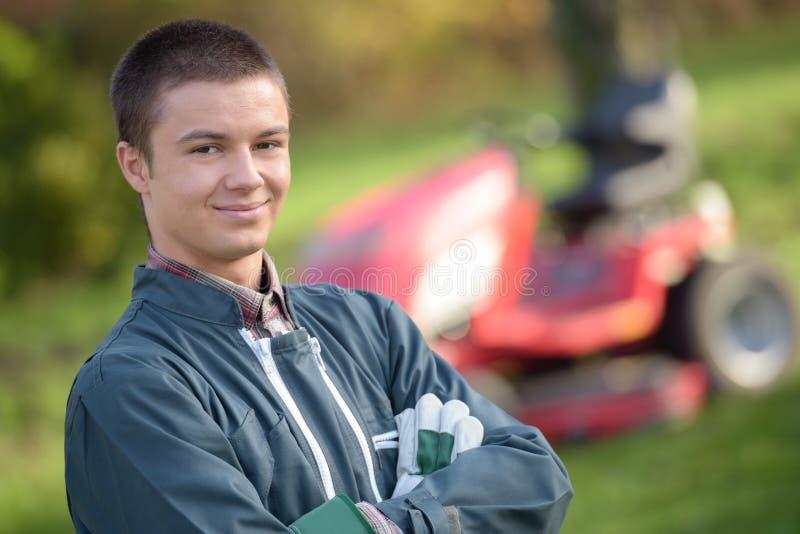 Gräsklippningsmaskin för ung man för stående i bakgrund fotografering för bildbyråer
