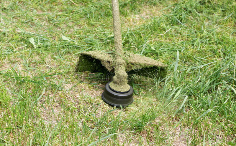 Gräsklippningsmaskinnärbild som mejar grönt gräs arkivfoto