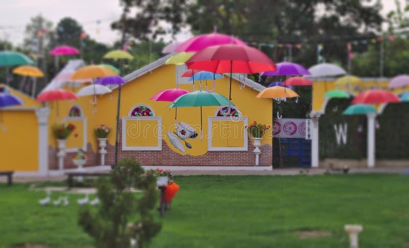 Gräsmattaträdgården som dekorerades med färgrika paraplyer, regnig säsong, den gamla cykeln, dekorerade målad europeisk bakgrund  royaltyfria bilder