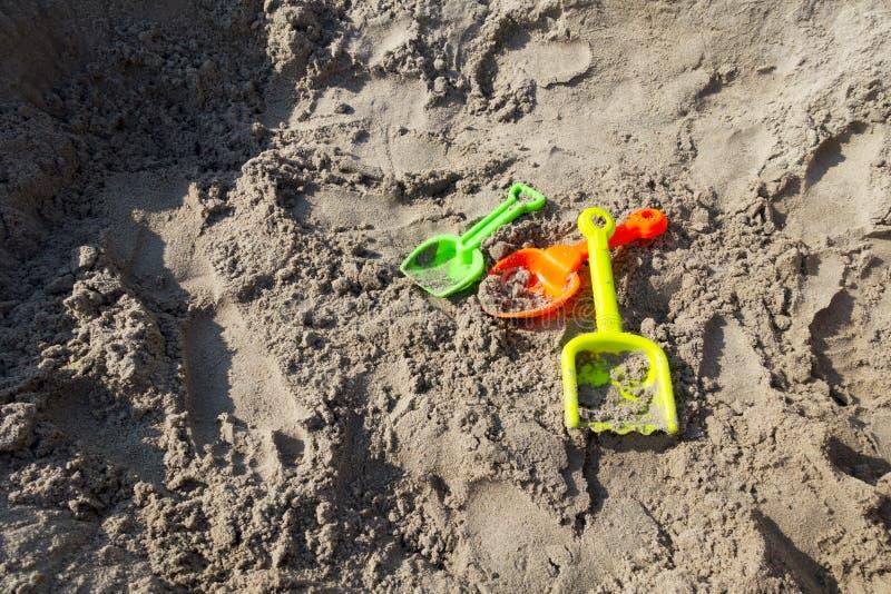 Gräsplan apelsin, gula plast- leksakskyfflar på stranden sandpapprar eller sandpapprar asken arkivbilder